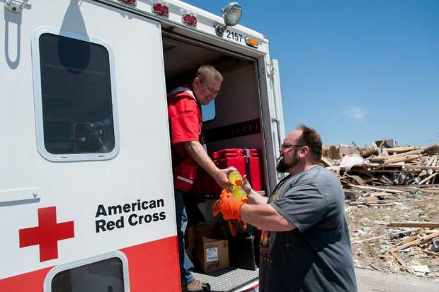 May 3, 2014. Mayflower, Arkansas. Red Cross emergency response vehicles (ERVs) delivered cleanup kits, rakes, shovels, gloves, garbage bags, tarps as well as snacks and water to residents and workers cleaning up after the tornado. Red Cross volunteer gives refreshments to local, Bart Gam. (Photo by Jason Colston/ American Red Cross)